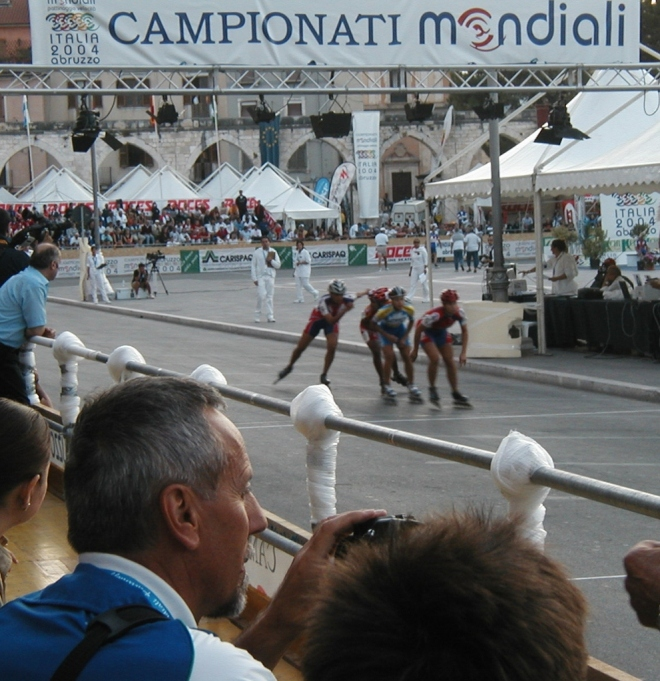 "A banner announces ""World Championships"" with Sulmona's iconic medieval aqueduct in the background."