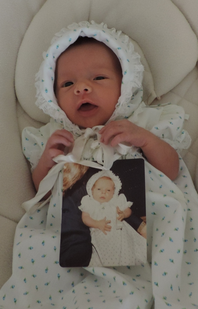 Grandbaby Cosette holding a photo of her mom wearing the same dress, both at age two weeks!