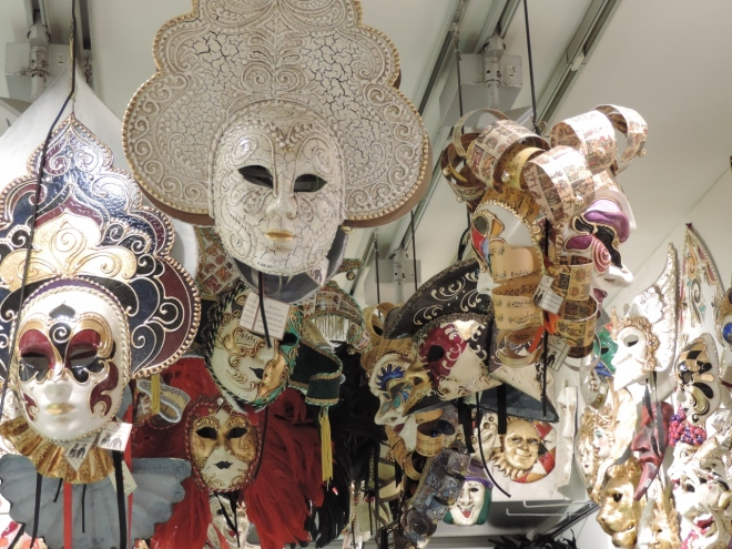 Masks hanging in a shop mimic the crowds at Carnevale.